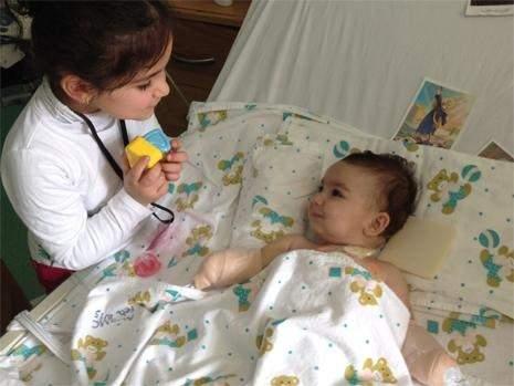 إيلا تبتسم في سريرها معوّلة على حركات عينيها وشفتيها لتعويض اليدين والقدمين