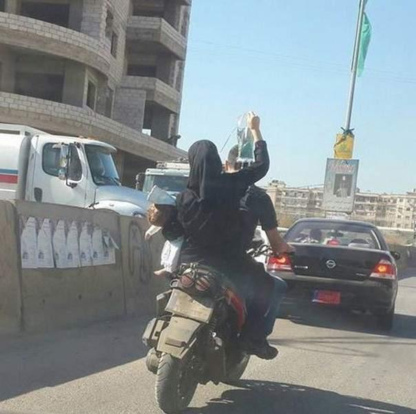 """صورة مؤثرة..أمٌ تحمل طفلها و""""المصل"""" على دراجة نارية"""