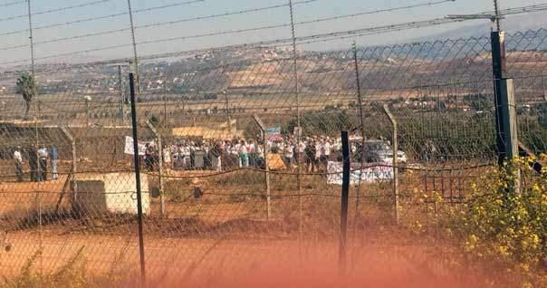 بالصورة: تجمع عشرات المستوطنين الإسرائيليين في مستعمرة المطلة مقابل طريق عام كفركلا - عديسة قرب السياج الحدودي الشائك رافعين لافتات تطالب بالسلام