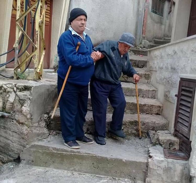 صورة معبرة...رجل ضرير يساعد مسناً في منطقة حقل العزيمة-الضنية وكل منهما يحمل عكازه