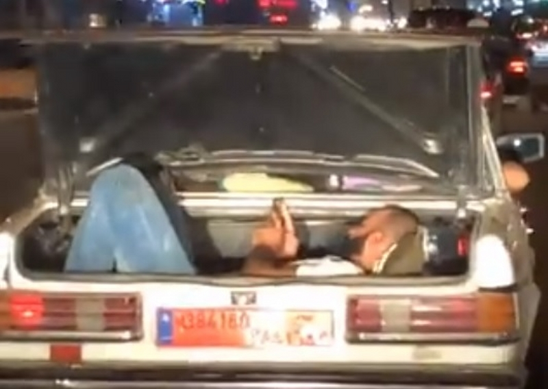 """فيديو """"صادم""""... مواطن مستلقٍ داخل """"صندوق السيارة"""" ويستخدم هاتفه """"بكلّ برودة"""" أثناء سير السيارة على أوتوستراد الضبية!"""