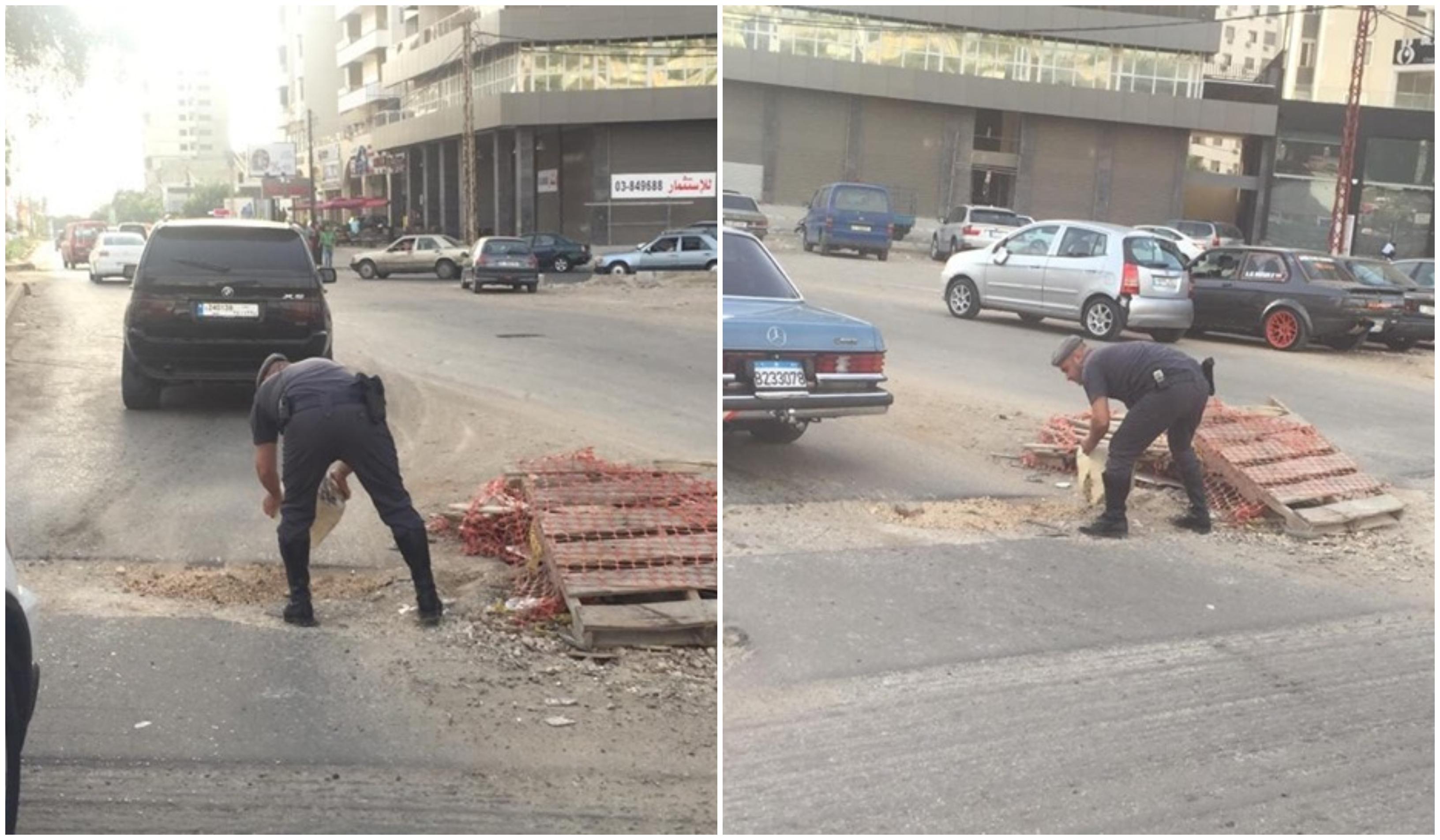 بالصور/ شرطي سير يساهم بتخفيف الحفر الموجودة على طريق البحصاص - طرابلس